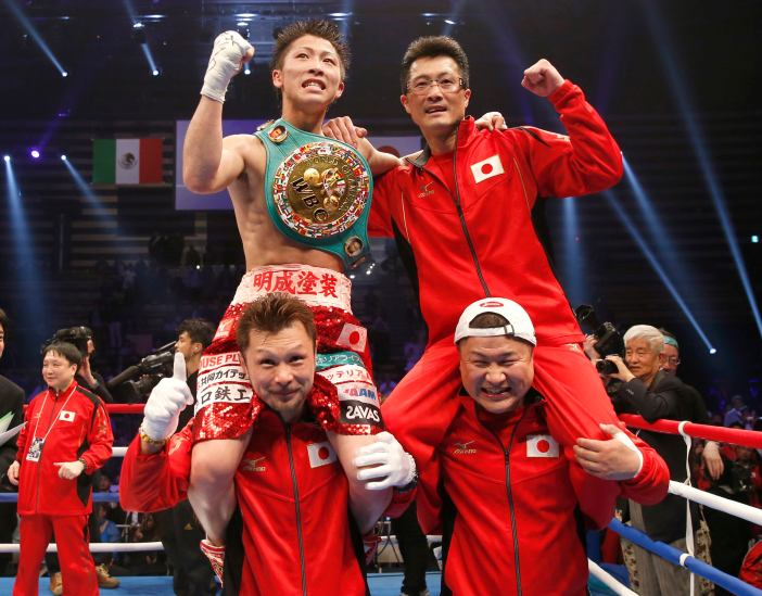Inoue celebrates with his father Shingo after defeating Hernandez during their WBC light flyweight title bout in Tokyo
